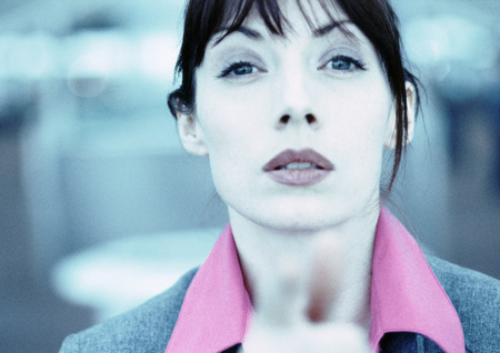 Businesswoman looking and pointing at camera, fingers blurred in foreground, close-up, cool toned