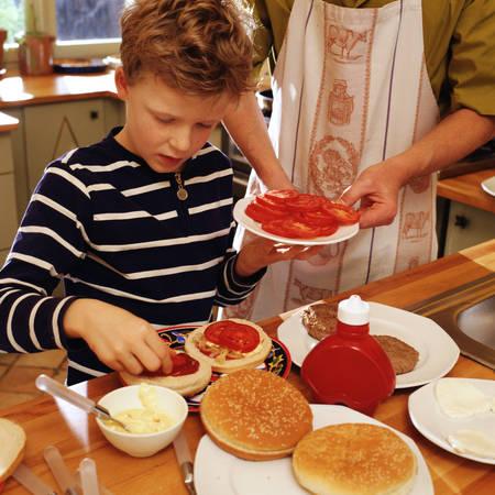 Child garnishing hamburgers, adult holding plate of tomato slices  LANG_EVOIMAGES