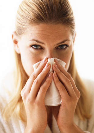 Woman blowing nose, close-up
