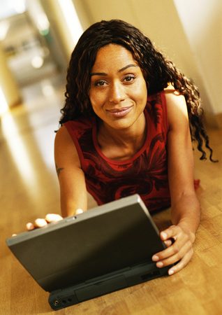Woman lying on floor with laptop computer, portrait