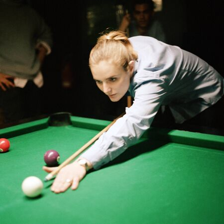 deftness: Young woman shooting pool, people standing in background