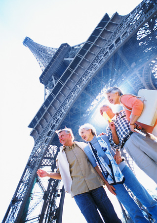 France, Paris, group of mature people standing in front of Eiffel Tower
