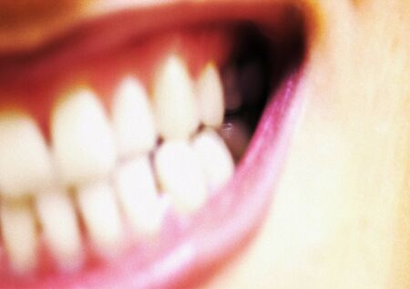 revolting: Extreme close-up of womans mouth, wide open, showing teeth, partial view, blurred