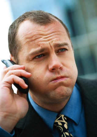 Businessman using cellular phone, puffing out cheeks and furrowing brow, portrait, close-up