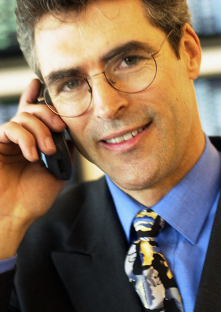Businessman wearing glasses using cellular phone, close-up, portrait