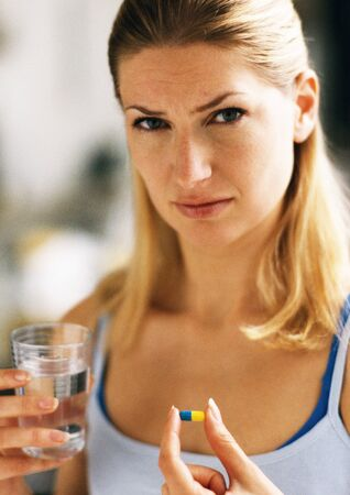 Woman holding pill and glass, looking at camera