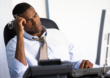 burned out: Businessman sitting at desk with eyes closed