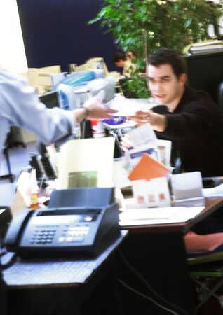 burned out: In office, man handing document to second person, blurred LANG_EVOIMAGES