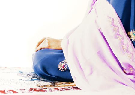 Moslemische Frau, die auf Gebetsteppich sitzt LANG_EVOIMAGES