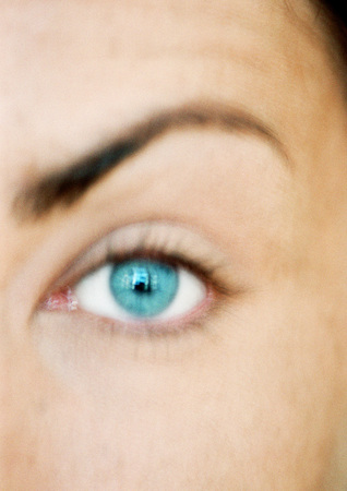 Womans blue eye and raised eyebrow, looking at camera, close-up, blurred