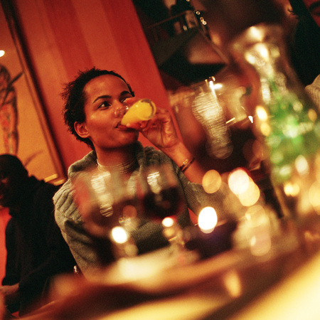 Young woman sitting at table, drinking, glasses blurred in foreground