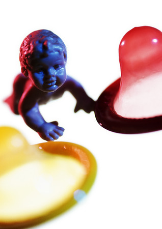 Plastic baby doll between condoms, close-up