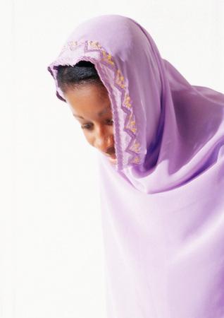 Frau, die den religiösen Schleier, unten schauend trägt LANG_EVOIMAGES