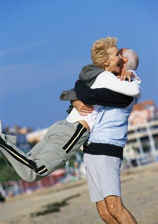 resort life: Mature man swinging mature woman on beach
