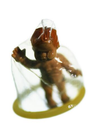 Plastic baby doll standing under condom, close-up
