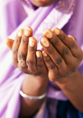 Schließen Sie oben von den Händen der moslemischen Frau im Gebet