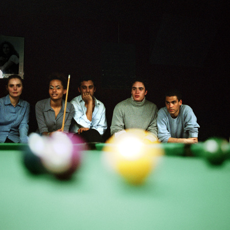 entertaining area: Group of young people watching a pool game, pool table blurred in foreground