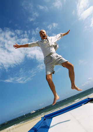 Mature man jumping on trampoline at the beach, arms out, mouth open