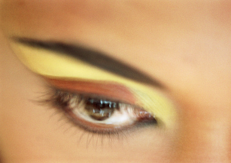 beauties: Womans eye with yellow and orange eye shadow, extreme close-up, blurred