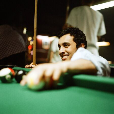 entertaining area: Young man retrieving balls from pool table