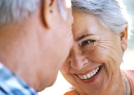 Mature man and woman smiling, close-up LANG_EVOIMAGES
