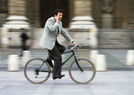 Man wearing suit, holding cell phone to ear and riding bike, blurred LANG_EVOIMAGES