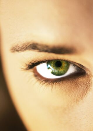 Womans green eye and eyebrow, extreme close up