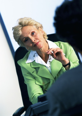Businesswoman sitting in armchair looking at person in blurred foreground