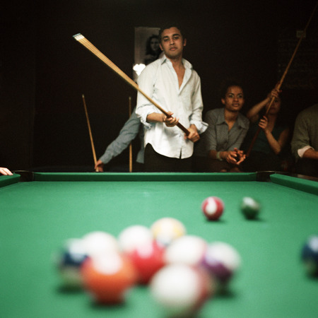 entertaining area: Young man shooting pool, people watching in background, billiard balls blurred in foreground