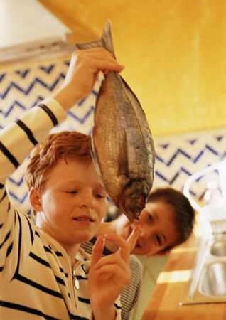 curiousness: Two children in kitchen, one holding up a fish