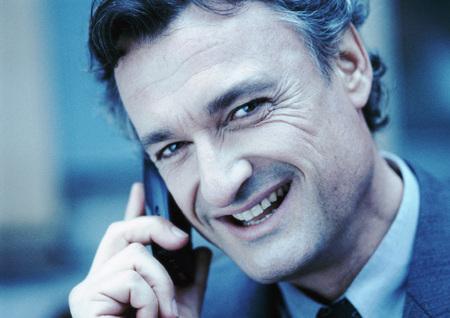 Businessman using cellular phone, smiling at camera, close-up, cool toned LANG_EVOIMAGES