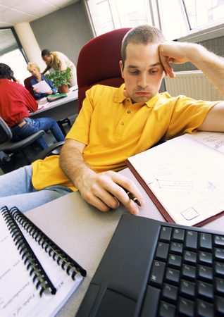 burned out: Young man sitting in office, slouching in chair, people working in background