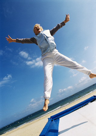 Mature woman jumping on trampoline at the beach, low angle view