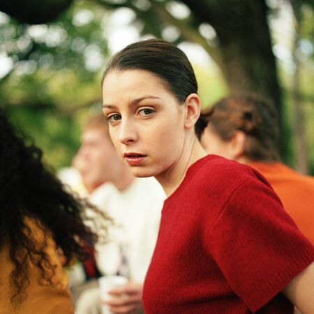desconfianza: Young woman looking at camera, people in background