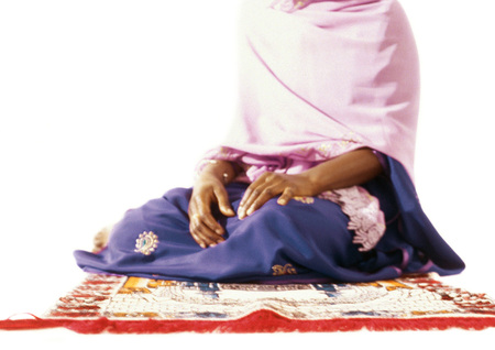 Muslim woman sitting on prayer rug