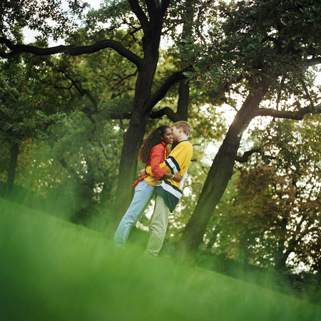smooching: Young man and woman standing on grass, embracing, side view, full length LANG_EVOIMAGES