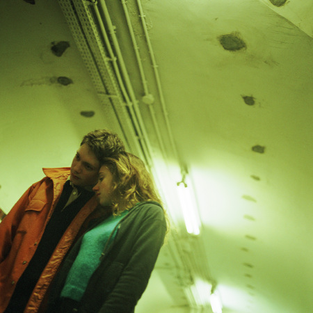 Young people leaning on each other in subway corridor