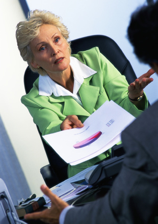 criticism: Businesswoman handing document to colleague, blurred foreground LANG_EVOIMAGES