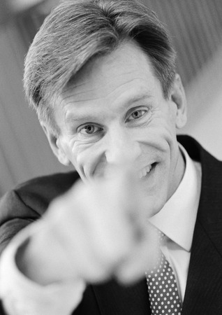 Businessman pointing at camera, hand blurred in foreground, black and white, close-up, portrait
