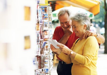 Mature man and woman looking at postcards in the street