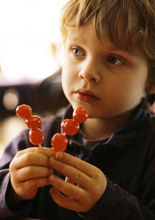 sucker: Little boy with cherries on sticks, portrait