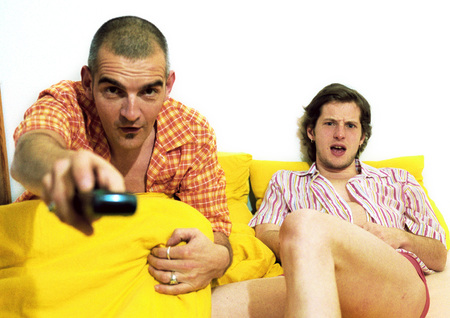 Two men sitting on sofa, one pointing remote control at camera