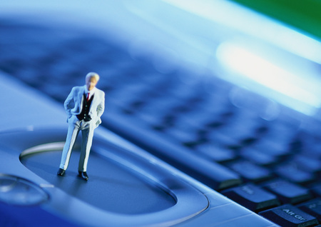 Small toy figure on computer keyboard, focus on figure, close-up