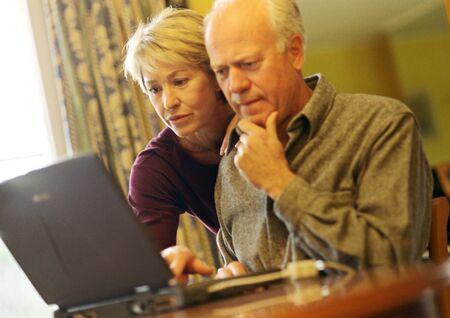 Mature couple, man using laptop, woman looking over shoulder LANG_EVOIMAGES