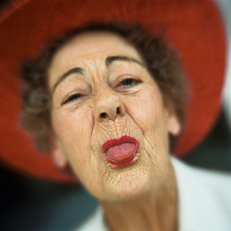 Portrait of senior woman wearing red hat with tongue sticking out LANG_EVOIMAGES