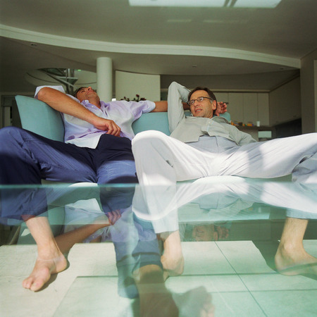 Two men with legs spread, sitting on sofa  LANG_EVOIMAGES