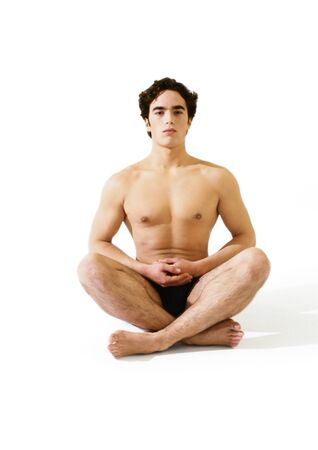 Man in underwear sitting indian style on floor with hands together LANG_EVOIMAGES
