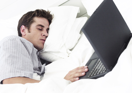 Man lying on bed with eyes closed, hand on laptop computer