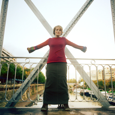 Woman standing on bridge with arms stretched out