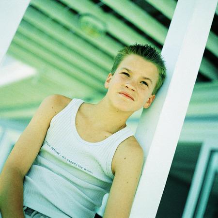 Teenage boy leaning back against post
